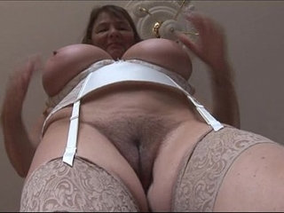 Busty mature brunette with huge boobs and hairy pussy strips